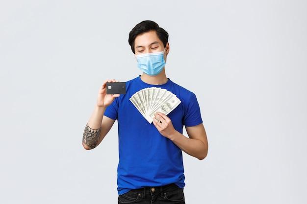 お金、covid-19、簡単な支払い、投資、銀行のコンセプト。医療マスクの若いアジア人が喜んで彼の収入と健康を守り、預金に現金を置き、クレジットカードに笑顔を好む