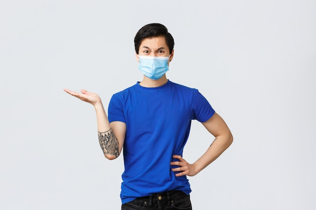 Covid-19とライフスタイルのコンセプト。怒っている不満の男性客、医療マスクのアジア人の男が左手を指し、しかめっ面の失望