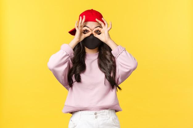 Covid-19、社会的距離のあるライフスタイルは、ウイルス拡散の概念を防ぎます。フェイスマスクと赤い帽子の面白いとかわいいアジアの女性、目の上の指で偽のメガネを作る、驚きと感銘を凝視