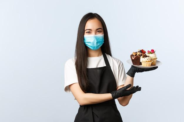 Covid-19、社会的距離、小さなコーヒーショップのビジネスとウイルスの概念を防ぎます。笑顔のかわいいアジアンカフェのオーナー、女性のバリスタまたはウェイトレスがプレートにマフィンを注文し、医療用マスクを着用