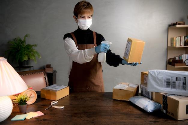 コロナウイルスcovid-19パンデミック時に小包や箱に消毒剤をスプレーする人