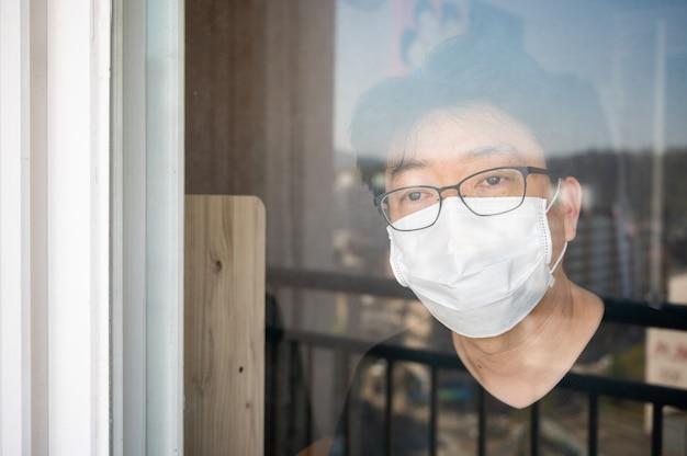 Концепция самоизоляции коронавируса covid-19. азиатский человек с лицевой маской и окном, смотрящим из окна во время его самоизоляции дома.