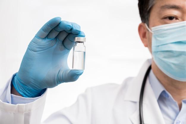 白い背景に青い手袋を着用し、covid-19ワクチンを持っている医師の手。