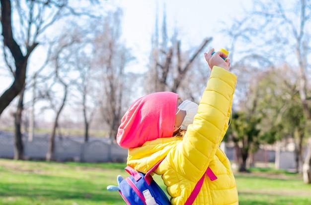 検疫中に防護マスクを着た少女が春に野外を歩き、子供用カメラで写真を撮ります。コロノウイルス、covid-19。