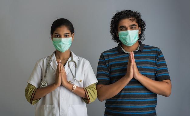 Covid-19の発生によりナマステをしている若い男女医師。ハグや握手で挨拶する代わりに、コロナウイルスの蔓延を回避する新しい挨拶。メンタルバランスのためのヨガの練習。