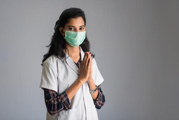 Covid-19の発生によりナマステを行う若い女性医師。ハグや握手で挨拶する代わりに、コロナウイルスの拡散を避けるための新しい挨拶。
