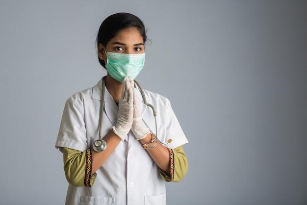 Covid-19の発生によりナマステをしている若い女性医師。ハグや握手で挨拶する代わりに、コロナウイルスの蔓延を回避する新しい挨拶。