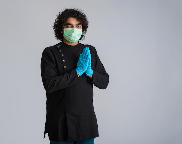 Covid-19の発生によりナマステをしている青年。ハグや握手で挨拶する代わりに、コロナウイルスの蔓延を回避する新しい挨拶。メンタルバランスのためのヨガの練習。
