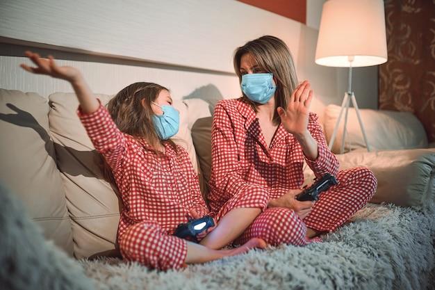 パジャマと医療用保護マスクを身に着けている女性と少女が、自宅のビデオゲームコントローラを備えたリビングルームのソファに座って、自動隔離、covid-19を使用しています。