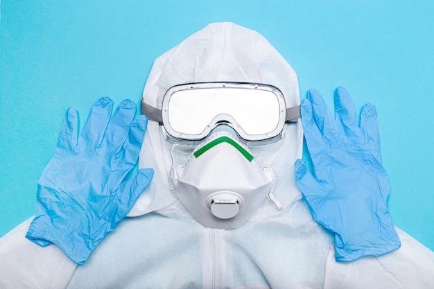 コロナウイルスcovid-19ウイルスの発生に対抗するための防護服。青色の背景に分離された安全服