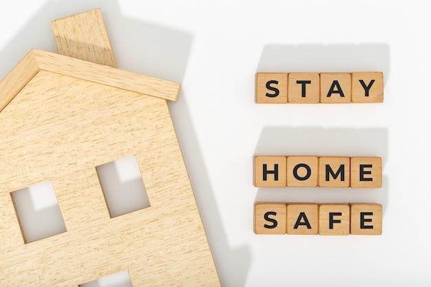 安全なコンセプトで家にいます。コロナウイルスcovid-19アウトブレイクアドバイス。ホームアイコンと白い背景の上の木製のブロック