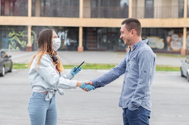ヨーロッパのウイルス性疾患の流行中のライフスタイル。 covid-19コロナウイルス、インフルエンザ。手術用の医療用マスクを着た少女と彼女の手に携帯電話をかぶった少女は、若い男に挨拶します。
