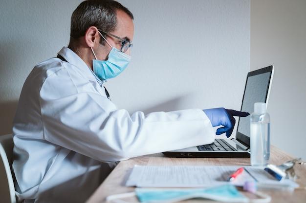 Доктор человек работает на ноутбуке. тест на вирус короны на столе. концепция covid-19