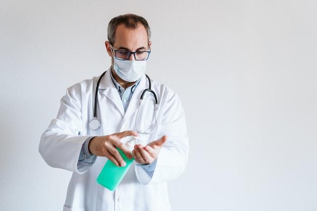 Человек доктора нося защитную маску внутри помещения. проведение спиртового геля или антибактериального дезинфицирующего средства. концепция гигиены и вируса короны. covid-19