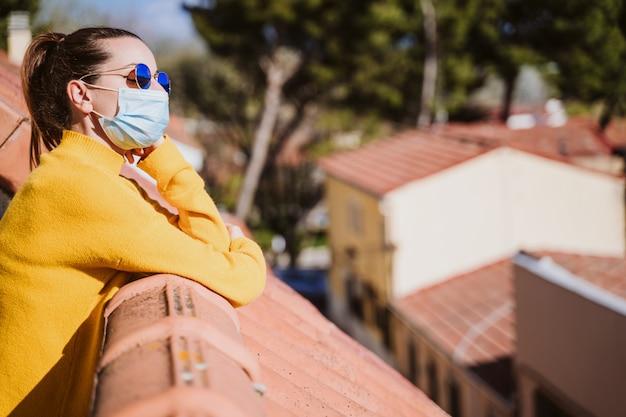 防護マスクを着用し、晴れた日を楽しんでいるテラスで自宅で若い女性。コロナウイルスcovid-19コンセプト