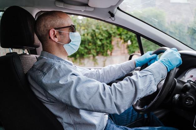 Мужчина за рулем автомобиля в защитной маске и перчатках во время пандемического коронавируса covid-19