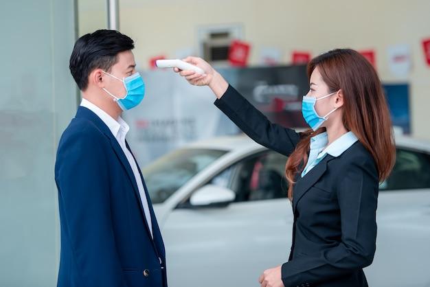 若いビジネスマンは、細菌や細菌の拡散を防ぐために、covid-19ウイルスが拡散した後、体温計を使用して体温を測定しています。