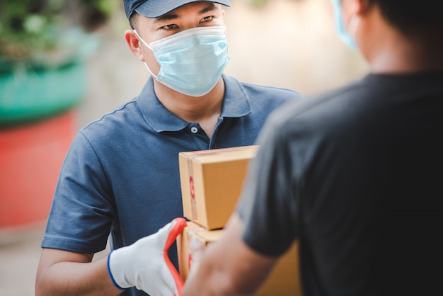 紙箱を運ぶ配達スタッフ。 covid-19を保護するために医療用手袋とマスクを着用してください