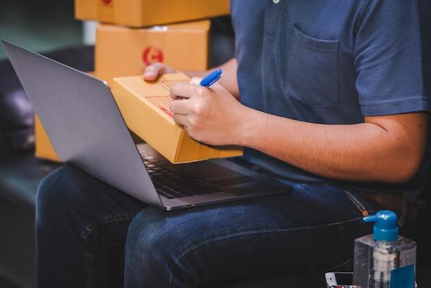 配送中のオンラインショッピングスモールビジネスの所有者は、中小企業家起業家のために職場で段ボール箱に書き込みます危機covid-19オンラインセールスビジネスの影響