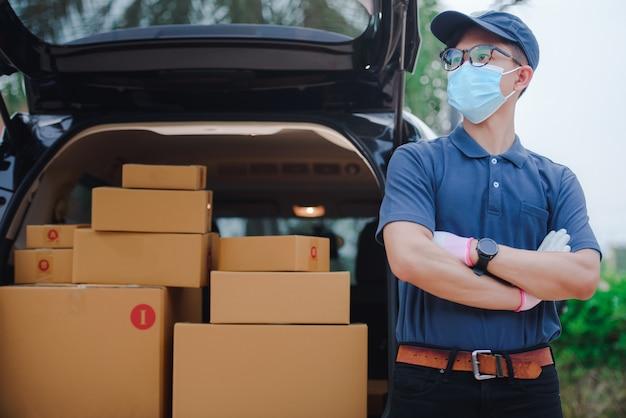 貨物車の後ろの配達人がコロナを保護するために医療用マスクを着用している、またはcovid-19がパッケージの配達中にマスクを着用している。