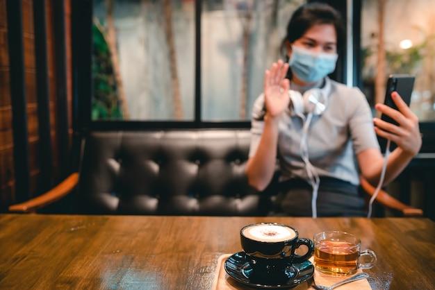 Covid-19を保護するために、電話で遊んでいるヘッドフォンと医療マスクを備えたコーヒーショップに女性が座っていました。