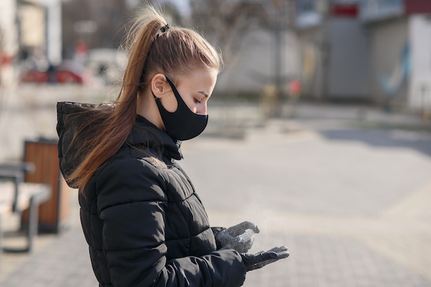 Красивая девушка стоит за столом со здоровой защитной маской для лица от коронавируса covid-19, распыляя дезинфицирующую жидкость на хирургические перчатки и ожидая пассажиров в аэропорту белграда.