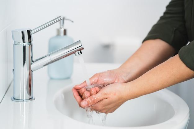 Гигиена. чистка рук. мыть руки с мылом. руки молодой женщины моя с мылом над раковиной в ванной комнате, крупном плане. covid 19. коронавирус.