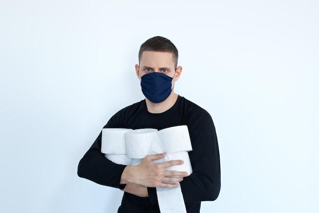 Covid-19、コンセプト検疫中にティッシュトイレットペーパーを保管する人。人々はコロナウイルスから家庭検疫用のトイレットペーパーを蓄えています。トイレットペーパーの多くのロールを持つ男。人々はパニックに陥ります。