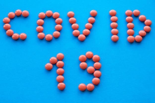 薬と綴られた単語covid-19。コロナウイルスの概念。ウイルスを止める。上面図