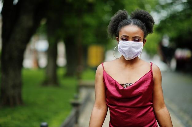 Covid-19, инфекционный вирус. африканская женщина с вьющимися волосами, носит красное шелковое платье и медицинскую одноразовую маску, заботится о своем здоровье и защищает в опасной ситуации.