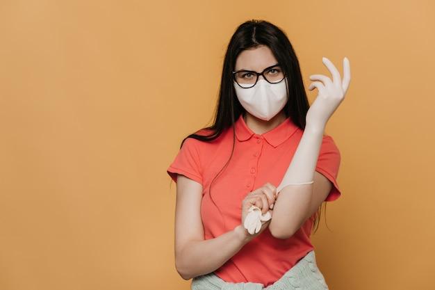 Молодая девушка в хирургической маске и очках, одетая в розовую футболку, надевающая защитные перчатки, выглядит уверенно, защитит от пандемии коронавируса, изолирует дома. концепция covid-19.