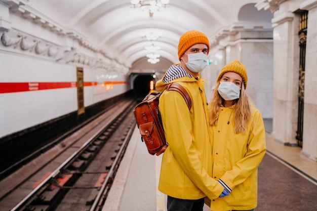 電車を待っている地下鉄の駅で黄色のウインドブレーカーに身を包んだ医療用防護マスクのカップル。パンデミック・コロナウイルスについての悲しい考え。 covid-19ウイルスのコンセプト。
