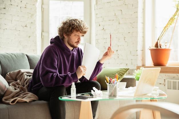 コロナウイルスまたはcovid-19検疫中に自宅で作業する男性