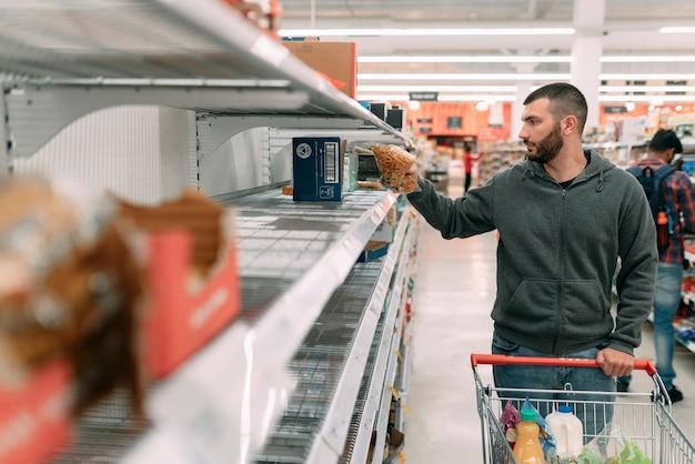 Человек изо всех сил пытается получить основные поставки в супермаркете, такие как спагетти, рис и другие макароны из-за панической покупки коронавируса (covid 19)
