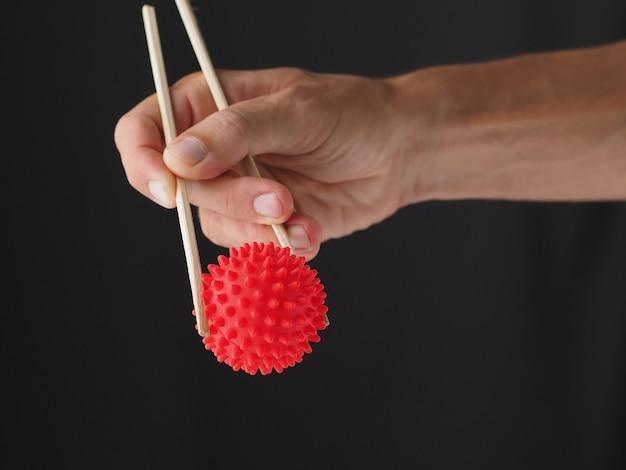 閉じる。男は、コロナウイルスcovid-19で中国の木製箸を保持しています。概念図。