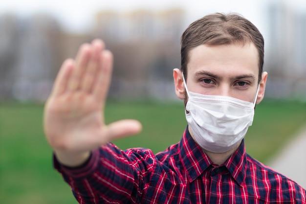男、彼の顔に防護医療マスクの若い男が屋外でカメラを見て、アジアのストリートショーの手のひら、手でサインを止めないでください。大気汚染、ウイルス、パンデミックコロナウイルスの概念。 covid-19