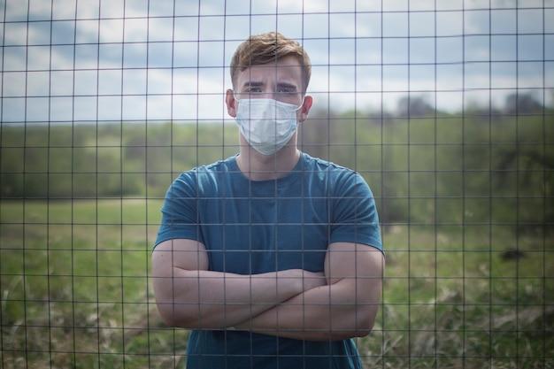 Заключенный гая в защитной маске на его лице изолировал положение за решеткой, решетку. ограничение свободы. самоизоляция, коронавирусная эпидемическая вирусная инфекция. covid-19. изолированный молодой человек в тюрьме