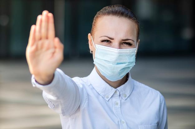 女の子、若い女性、顔に保護滅菌医療マスクの女性実業家、手のひら、手、兆候を停止します。大気汚染、ウイルス、パンデミックコロナウイルスの概念。 covid-19