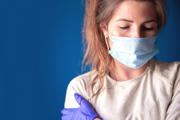 Covid-19コロナウイルスのために、家の中で退屈で悲しい探している保護手袋とフェイスマスクを身に着けている若い女性