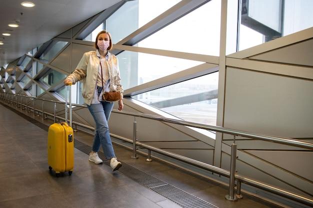 ほとんどの空港/旅行駅を歩いている荷物を持ってコロナウイルスが歩くのを防ぐために医療用保護マスクを着用している乗客の女性。旅行禁止、covid-19の発生。