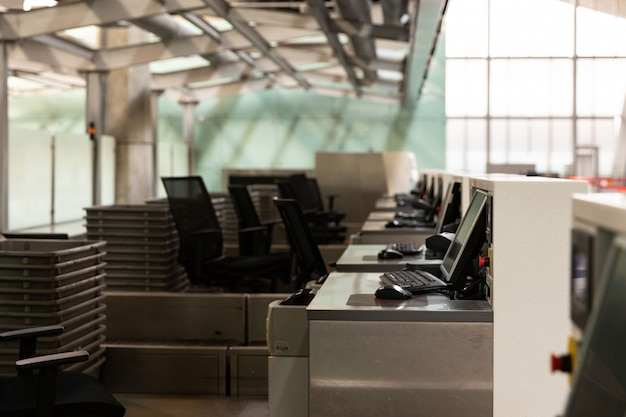 コロナウイルスのパンデミック/ covid-19の発生により、空の空港ターミナルにコンピューターモニターを備えたチェックインデスクの列。