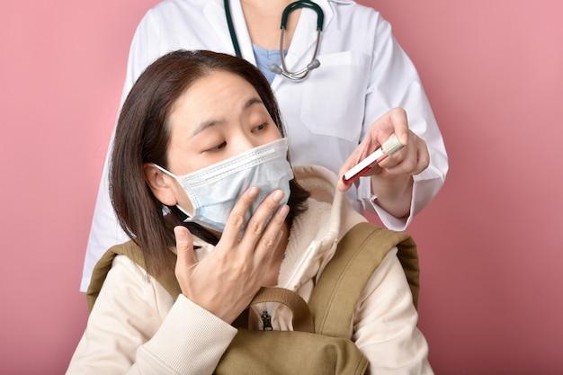 コロナウイルス陽性の血液検査、アジアの女性が病気の血液スクリーニングの結果に衝撃を与えた、医師が病院でcovid-19に感染した患者をスクリーニングしている。