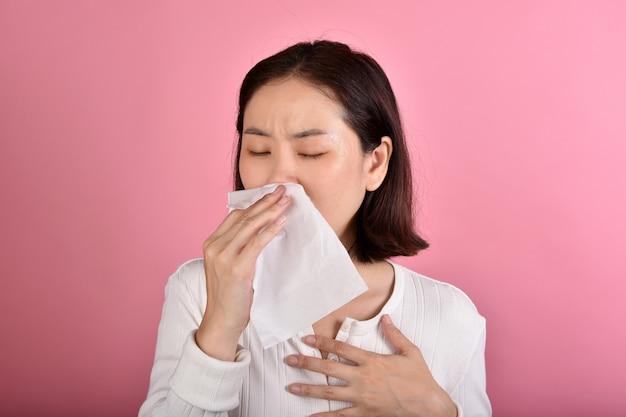 Азиатская женщина страдает аллергией на горло и кашлем, чиханием и кашлем в общественных местах без защиты распространяемой капли коронавирусной болезни (covid-19)