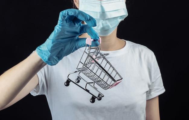 医療用防護マスク、黒い壁にミニスーパートロリーを保持している手袋の女性。パンデミックcovid-19でのショッピング