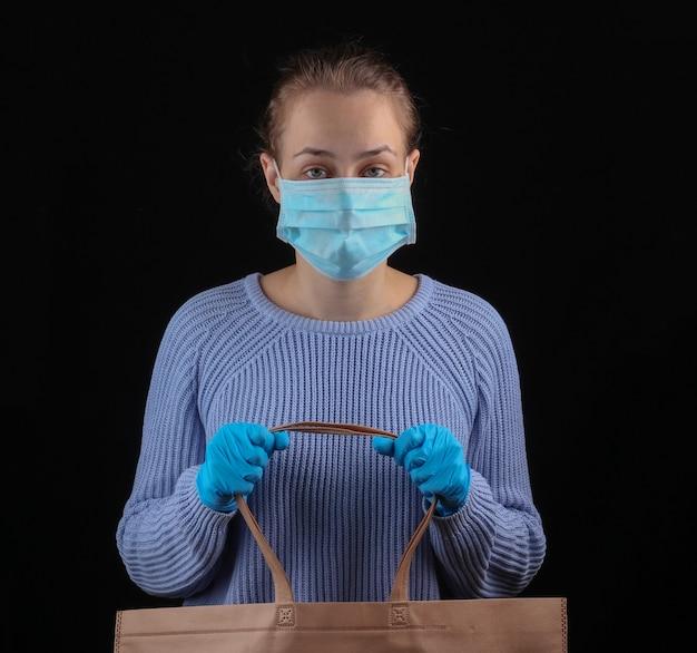 Covid-19パンデミック時のショッピング。医療マスクと手袋の女性は黒い壁にスーパーマーケットでの買い物のためのバッグを保持します