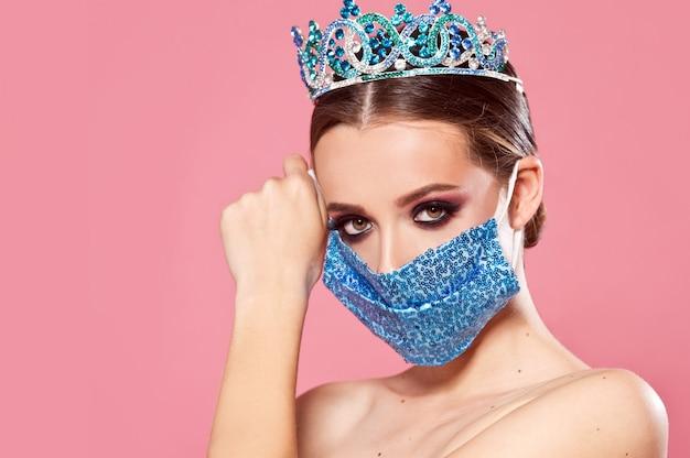 Covid-19を停止します。王冠とスパンコールのついたマスクの女の子。リモートで美容コンテスト。ファッションと美しさ。美の女王。