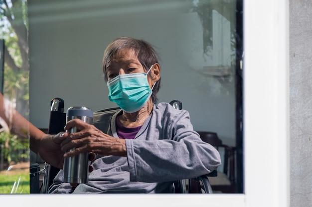 コロナウイルス(covid-19)の感染を外から守るために年配の女性が家にいる