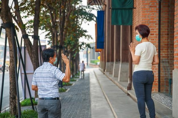 Covid-19の蔓延を避けるためにマスクを着用し、社会的距離を保つアジアの中年の人々
