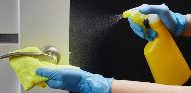 Covid-19中のウイルス感染を防ぐための白いドア消毒とスプレーのドアハンドル。