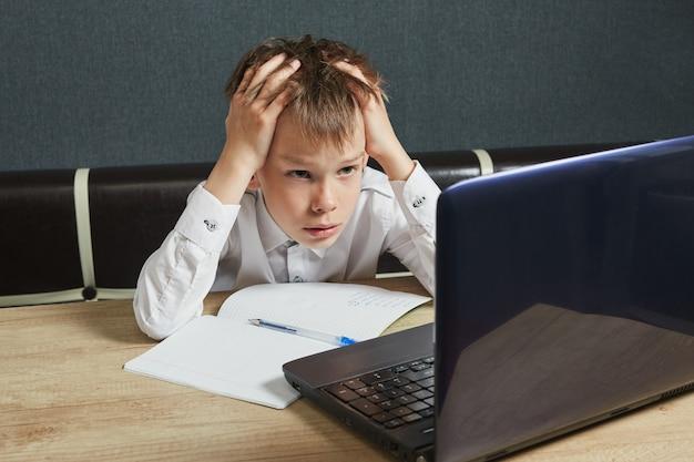 社会的な遠隔学習とオンライン教育の概念。宿題にラップトップを使用している子供。子供はcovid-19の間に家にいます